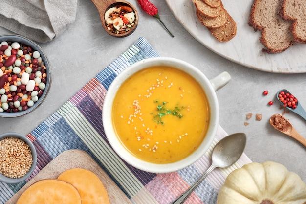Potage à la citrouille, haricots mélangés et crème de patates douces dans un bol en céramique, vue de dessus avec les ingrédients