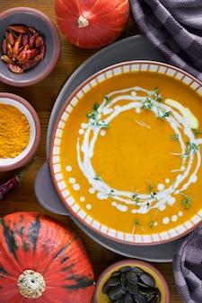 Potage à la crème de potiron dans un bol en céramique assaisonné de crème et de germes de cresson sur bois