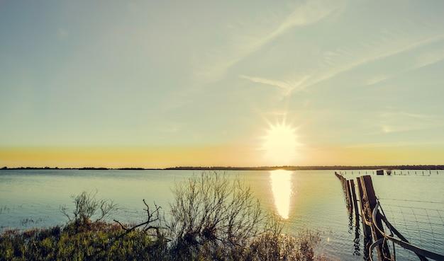 Poteau en bois à l'intérieur du lac avec des reflets de soleil dans l'eau au crépuscule