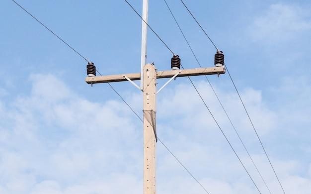 Poteau électrique en béton sous le ciel bleu.
