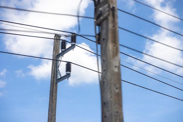 Poteau électrique et ligne électrique par temps clair avec ciel bleu et nuages blancs en arrière-plan.