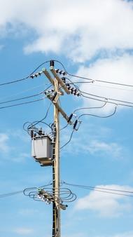 Poteau électrique et transformateur sur un ciel bleu
