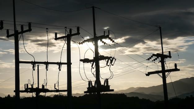 Les poteaux électriques contrastent avec le ciel au coucher du soleil le soir.