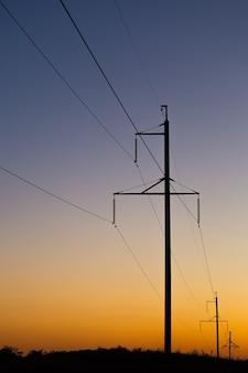 Poteaux électriques avec des fils dans la soirée au coucher du soleil