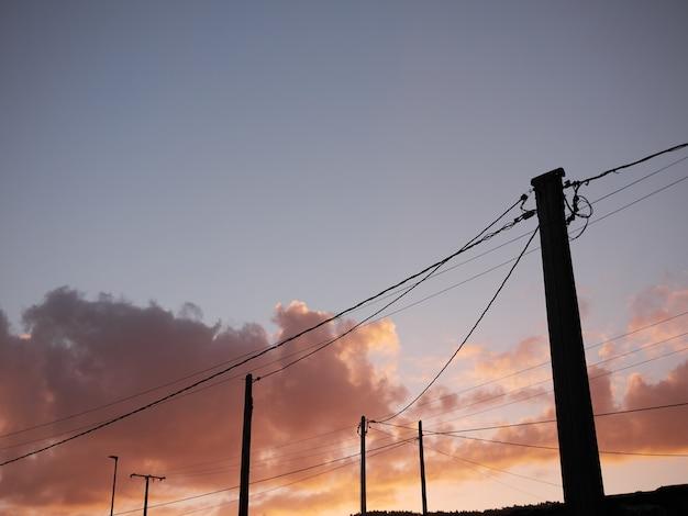 Poteaux électriques avec plusieurs fils et câbles dans la rue