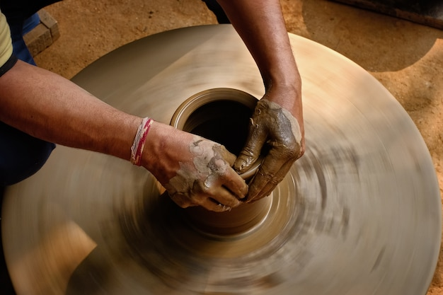Poterie - mains humides qualifiées de potier façonnant l'argile sur un tour de potier
