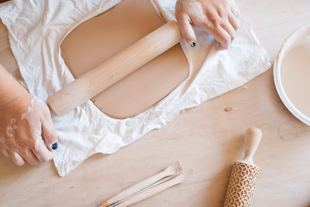 Potier femelle dérouler le foarm avec un rouleau à pâtisserie, atelier de poterie. matériel de travail de moulage de femme.