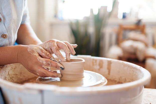 Potier femelle faisant un pot sur le tour de potier. femme moulant un bol.