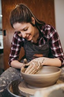 Potier femelle faisant de la poterie en argile sur une roue de rotation.