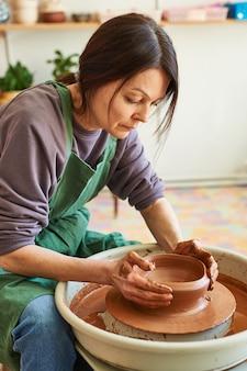 Potier femme en tablier vert travaillant sur un cercle avec de l'argile rouge.