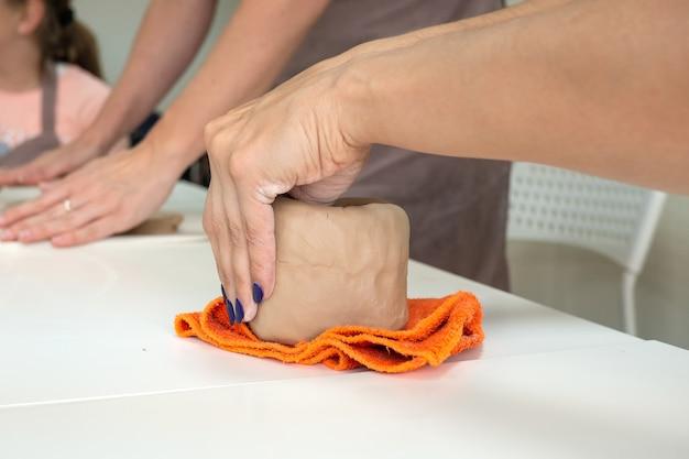Potier de main de femme faisant la tasse d'argile en studio d'atelier de poterie