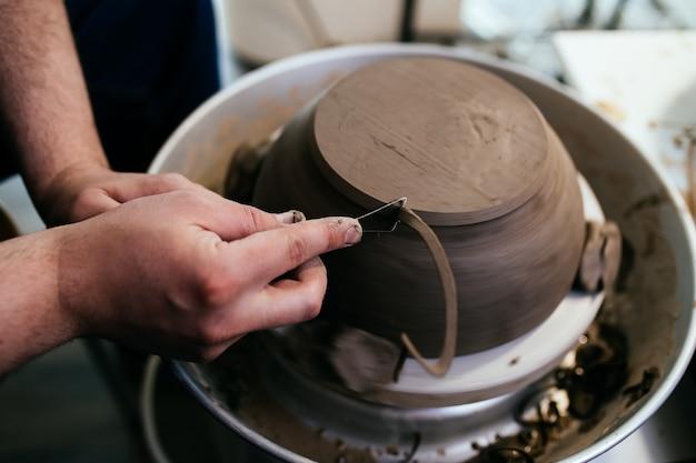 Potier masculin faisant de la poterie en argile sur une roue tournante.