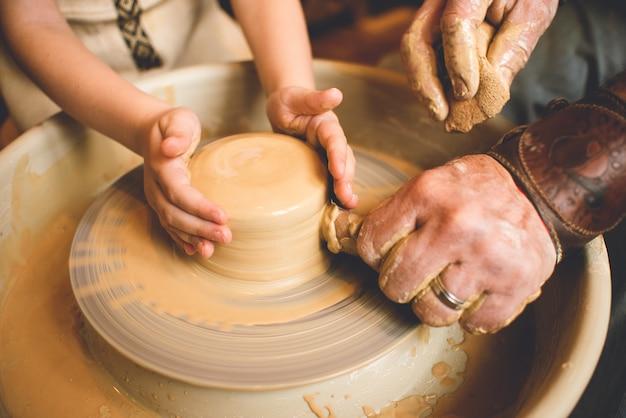 Potier professionnel faisant bol dans l'atelier de poterie