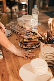Des potières arrangeant la palette en céramique sur une table en bois