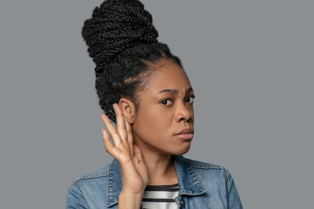 Potins. photo d'une jeune femme à la peau foncée touchant son oreille dans un geste d'écoute