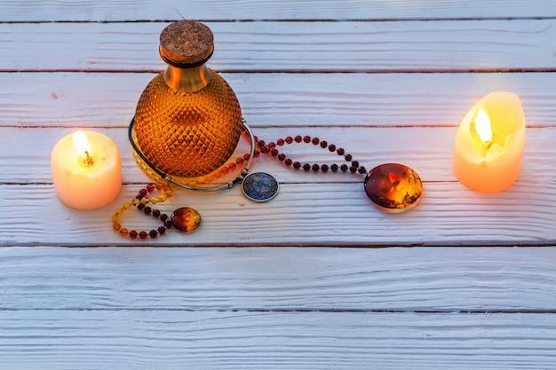 Potion magique et collier d'ambre sur fond de bois bleu