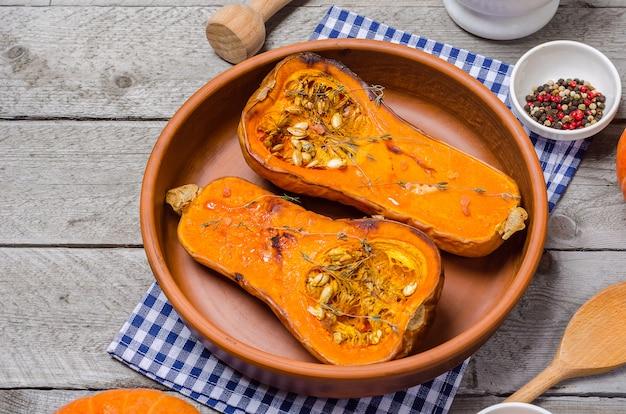 Potiron cuit au four avec du thym dans un plat en argile sur une serviette bleue, sur une table en bois