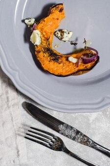 Potiron cuit au four avec gorgonzola sur plaque grise.