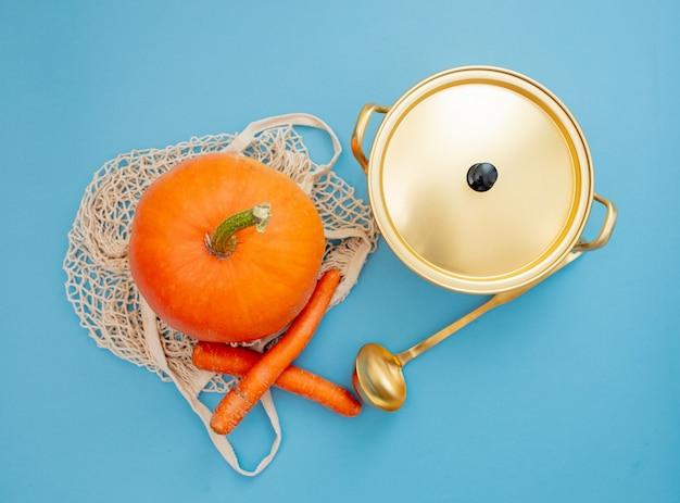 Potiron dans un sac en filet près de carottes et pan