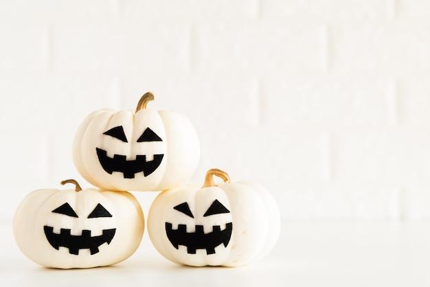 Potiron fantôme blanc sur fond de bloc de briques blanches. concept d'halloween