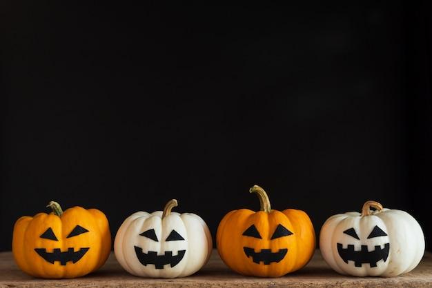 Potiron fantôme blanc et jaune sur fond noir. concept d'halloween