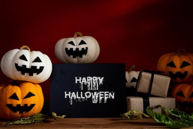 Potiron fantôme blanc et jaune sur une table en bois avec batte sur fond orange.