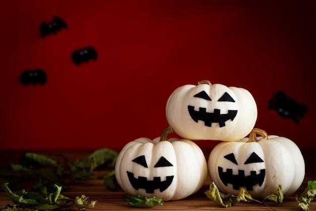 Potiron fantôme blanc sur table en bois avec batte sur fond orange