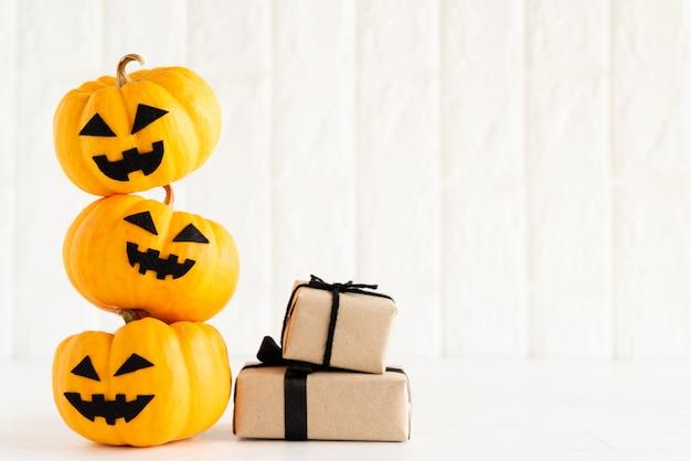 Potiron fantôme jaune avec boîte-cadeau sur fond de bloc de briques blanches.