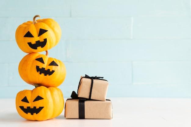 Potiron fantôme jaune avec boîte-cadeau sur fond en bois cyan