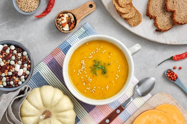 Potiron, haricots mélangés et soupe de crème de patate douce dans un bol en céramique, vue de dessus avec des ingrédients