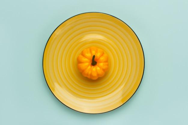 Potiron sur un plat jaune sur turquoise pastel.