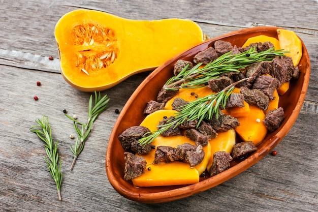 Potiron tranché cuit au four avec de la viande dans un pot en argile. repas d'automne au romarin et épices