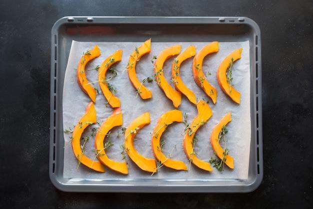 Potiron tranché avec thym, huile d'olive et sel dans une lèchefrite. délicieux casse-croûte. modèle de nourriture.