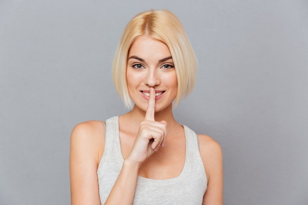 Potrait de femme blonde faisant un geste de silence
