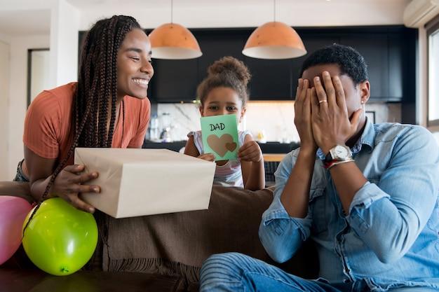 Potrait d'un père surpris de recevoir un cadeau de sa femme et de sa fille alors qu'il restait à la maison