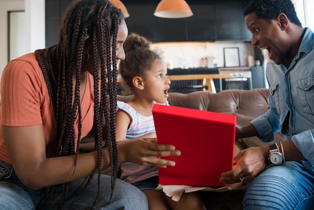 Potrait d'une petite fille surprise de recevoir un cadeau de ses parents tout en restant à la maison.