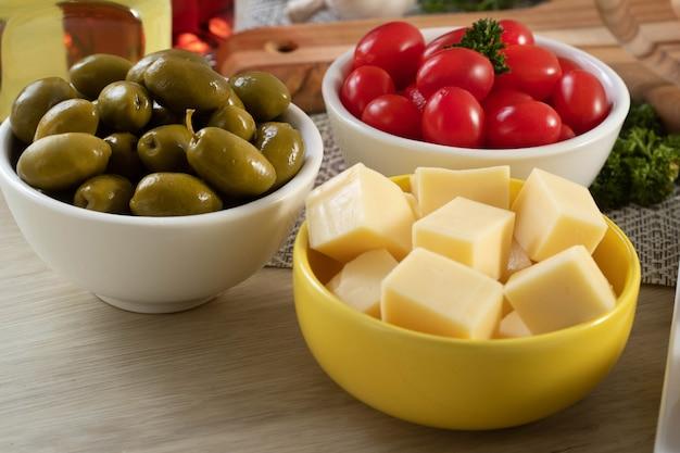 Pots d'apéritif avec du fromage, des olives et des tomates cerises.