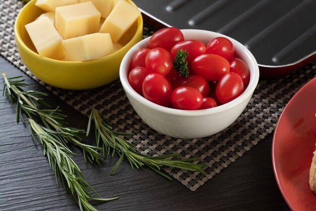 Pots d'apéritif avec du fromage et des tomates cerises.
