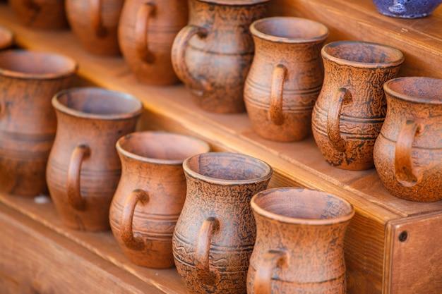 Des pots en argile brune se tiennent sur une étagère en bois
