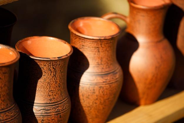 Des pots en argile brune sont alignés. fait main