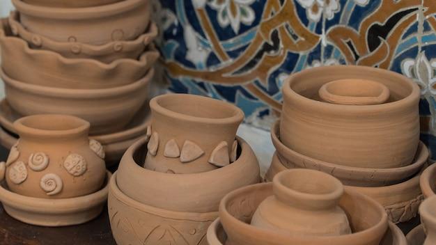 Pots en argile fraîchement préparés sur fond de mosaïque décorative. bricolage pour enfants