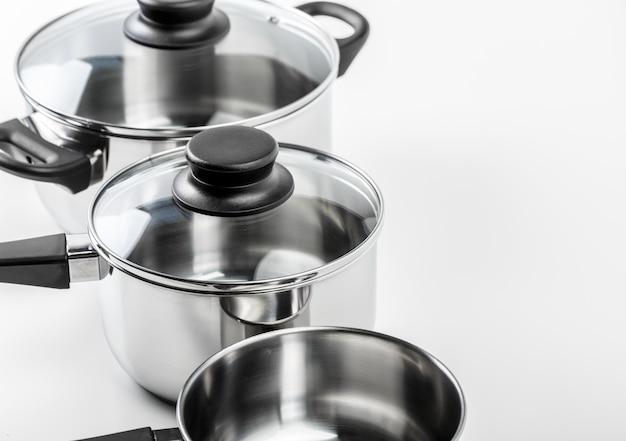 Pots et casseroles en acier inoxydable isolés sur blanc