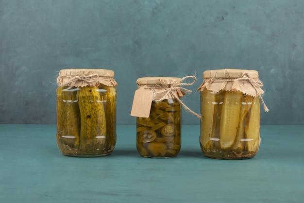 Pots de concombres et jalapenos marinés sur table bleue.