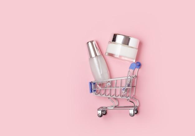 Pots cosmétiques blancs avec de la crème se trouvent dans un caddie sur rose