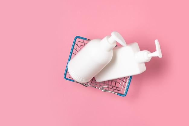 Les pots cosmétiques blancs se trouvent dans un panier sur rose