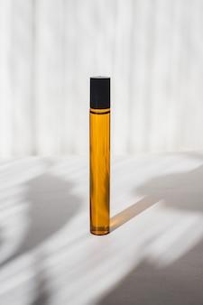 Pots cosmétiques avec des huiles sur fond blanc lumière et ombres minimalisme