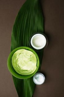 Pots de crème blanche hydratante et de gel d'aloès vert sur une feuille de palmier. différentes crèmes hydratantes pour différentes zones du visage sur un brun