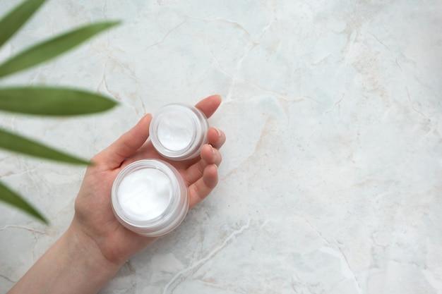 Pots de crème cosmétique à la main femme tenant un récipient blanc avec fond de marbre hydratant