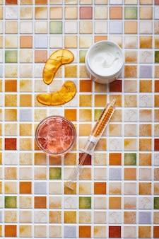 Pots de crème et de gel pour les soins du visage et du corps, des patchs pour les yeux en or et du sérum en or en tube de seringue
