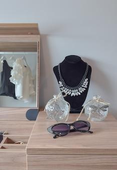 Pots de cristal et collier sur coiffeuse en bois